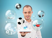 Adult handsome man holding tablet computer. Icons of different object are flying around. — Stock Photo