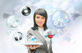 Pretty business woman holding tablet computer and different objects are flying from touch screen — Stock Photo