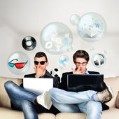 Two young gamers sitting together on sofa and using their laptop — Stock Photo