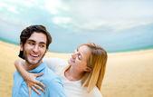 Porträtt av ungt par i kärlek omfamna på stranden och njuter av — Stockfoto