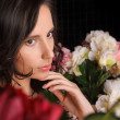 Portrait of young gorgeous woman with flowers at dark room with - Stock Photo