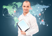 Adult man holding tablet computer against world map and server p — Stock Photo