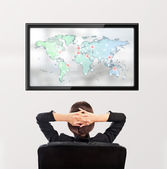 Woman watching tv. Photo from behind. Worldmap at the screen — Stock Photo