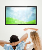 Young couple watching tv. Photo from behind. Lots of copyspace — Stock Photo