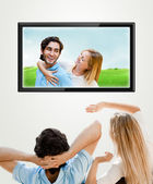 Young couple watching their photos on wide screen tv at home — Stock Photo