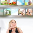 Stock Photo: Young woman has images around her head representing entertainmen