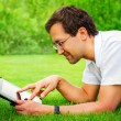 Adult man working with tablet computer outdoor in park — Stock Photo