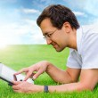 Adult man at summer park resting on weekend using his tablet com — Stock Photo #12033652