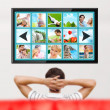 Man watching tv. Photo from behind. Editable copyspace at the sc - Stockfoto