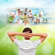 Young man standing in front of virtual preview of different imag — Stock Photo #12033690