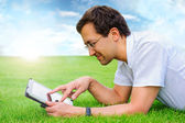 Adult man at summer park resting on weekend using his tablet com — Stock Photo