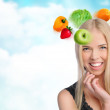 Young beautiful woman with vegetables, berries and fruits flying around her head — Stock Photo #12147421
