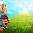 Foto Stock: Young woman running across beautiful field to the bright luminous door on a hill