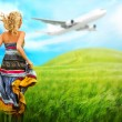 Woman running across field with idyllic landscape. Airplane and birds are flying in the sky - Stock Photo