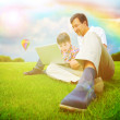 adult man and his little son sitting on a grass at park and havi — Stock Photo
