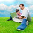 Father and son at park smiling and having fun with laptop - Photo