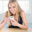 Young smiling woman using her laptop at home — Stock Photo
