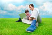 Father and son at park smiling and having fun with laptop — Stock Photo