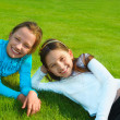 Two sisters laughing and playing in the park, laying down. — Stock Photo