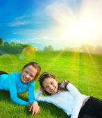 Two little sisters are resting on grass against idyllic landscap — Stock Photo