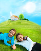 Two young girls laying down on grass and smiling. Beautiful hous — Stock Photo