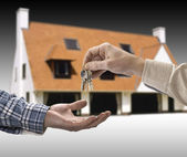 Man is handing a house key to a other man in the shape of the ho — Stock Photo