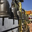 Thailand, Chiang Mai, Prathat Doi Suthep Buddhist temple, a Thai woman plays the religious bells of the Buddhist temple — Stock Photo