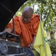 Thailand, Chiang Mai, a Buddhist monk is trying to fix his old car's engine - Foto de Stock