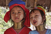 Thailand, Chiang Mai, Karen Long Neck hill tribe village (Kayan Lahwi), Long Neck young girls in traditional costumes. Women put brass rings on their neck when they are 5 or 6 years old and increase t — Zdjęcie stockowe