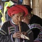 Thailand, Chiang Mai, Karen Long Neck hill tribe village (Kayan Lahwi), Karen man in traditional costumes playing a flute — Stock Photo #11312052