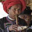 Thailand, Chiang Mai, Karen Long Neck hill tribe village (Kayan Lahwi), Karen man in traditional costumes playing a flute — Stock Photo