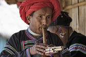 Thailand, Chiang Mai, Karen Long Neck hill tribe village (Kayan Lahwi), Karen man in traditional costumes playing a flute — Stock Photo
