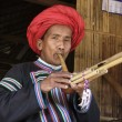 Thailand, Chiang Mai, Karen Long Neck hill tribe village (Kayan Lahwi), Karen man in traditional costumes playing a flute — Stock Photo #11369036