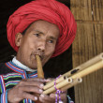 Thailand, Chiang Mai, Karen Long Neck hill tribe village (Kayan Lahwi), Karen man in traditional costumes playing a flute — Stock Photo #11369085