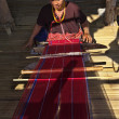 Thailand, Chiang Mai, Karen Long Neck hill tribe village (Kayan Lahwi), a Karen woman in traditional costumes is making a carpet — Stock Photo