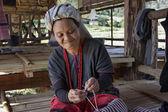 Thailand, Chiang Mai, Karen Long Neck hill tribe village (Kayan Lahwi), a Karen woman in traditional costumes is making a carpet — Stock Photo