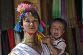 Thailand, Chang Mai, Karen Long Neck hill tribe village (Kayan Lahwi), Long Neck child and her mother in traditional costumes. Women put brass rings on their neck when they are 5 or 6 years old and in — Stock Photo