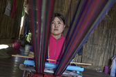Thailand, Chiang Mai, Karen Long Neck hill tribe village (Kayan Lahwi), Karen woman in traditional costumes is making a carpet — Stock Photo