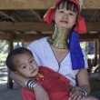 Thailand, Chang Mai, Karen Long Neck hill tribe village (Kayan Lahwi), Long Neck child and his mother in traditional costumes. Women put brass rings on their neck when they are 5 or 6 years old and in — Stock Photo #11485545
