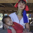 Thailand, Chang Mai, Karen Long Neck hill tribe village (Kayan Lahwi), Long Neck child and his mother in traditional costumes. Women put brass rings on their neck when they are 5 or 6 years old and in - Stock Photo