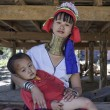 Stock Photo: Thailand, Chang Mai, Karen Long Neck hill tribe village (KayLahwi), Long Neck child and his mother in traditional costumes. Women put brass rings on their neck when they are 5 or 6 years old and in