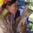 Stock Photo: Thailand, Chiang Mai, Karen Long Neck hill tribe village (BaTong Lhoung), Long Neck womin traditional costumes reading magazine. Women put brass rings on their neck when they are 5 or 6 years