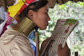 Thailand, Chiang Mai, Karen Long Neck hill tribe village (Baan Tong Lhoung), Long Neck woman in traditional costumes reading a magazine. Women put brass rings on their neck when they are 5 or 6 years — Stock Photo