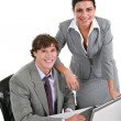 Stock Photo: Two Smiling Young Businesspeople Working in Office