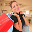 Happy smiling female shopper holding shopping bags — Stock Photo
