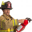 Stock Photo: Firefighter in uniform holding fire extinguisher