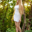 The beautiful blonde in a short white dress — Stock Photo