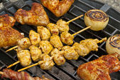 Barbecue with chicken wings, meat skewer and ham — Stock Photo