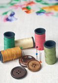 Many bobbin of thread with needle and button — Stock Photo