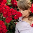 Young woman in flower garden smelling red roses — Stock Photo #12147865